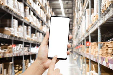 Close-up hands using smartphone in warehouse industry blur background for logistic wholesale storehouse, Online shopping concept. Mockup blank white screen mobile phone with finger point and touch on touchsreen with blurred warehouse.