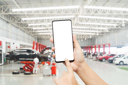 Mock up smartphone for automobile online service mobile application. Mockup blank white screen mobile phone with finger point and touch on touchsreen in  Auto repair shop. Stockfoto