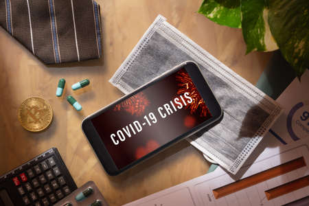 Coronavirus or Covid-19 business and econamic crisis background concept. Mockup mobile phone with facial masks and medical tablets on businessman's office wood desk table.