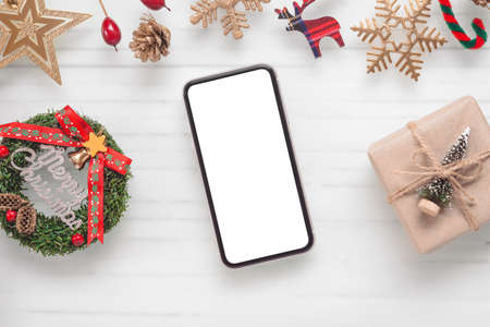 Mockup blank white screen smartphone on white desk background for Christmas, Flat lay top view with copy space for your Merry Christmas artwork. Zdjęcie Seryjne