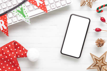 Mockup blank white screen smartphone on home office desk background for Christmas party background concept
