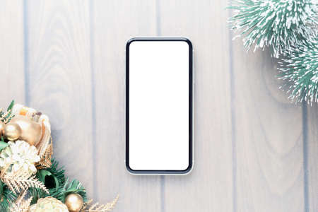 Mockup Smartphone with blank screen in Christmas frame. Merry Christmas and Happy New year background with empty smartphone on wood table background, copy space for text or advertisement. Zdjęcie Seryjne