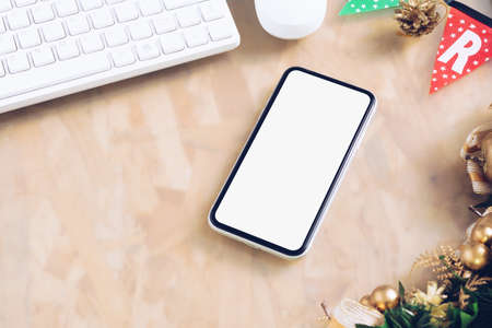 Mockup blank white screen smartphone on home office desk background for Christmas and New Year party background concept, Flat lay top view with copy space for your Merry Christmas and Happy New year artwork.