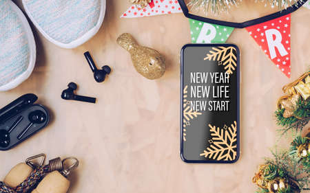 New Year New Life New Start text on mobile phone on table with sport shoes, wireless earphone and Christmas ornaments. Zdjęcie Seryjne