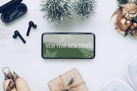 New Year New Start text on mobile phone on table with sport shoes, wireless earphone and Christmas ornaments. Zdjęcie Seryjne