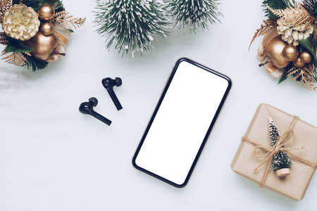 Mockup blank white screen smartphone on home office desk background for Christmas and New Year party background, Flat lay top view with copy space for your Merry Christmas and Happy New year artwork. Zdjęcie Seryjne