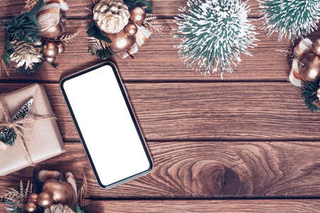 Mockup smartphone with blank white screen, new year gift box with Xmas pine tree model, christmas ornaments on wood background, top view, place for your artwork
