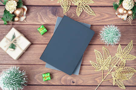 Mockup blank black book cover with Christmas gift box, Xmas ornaments and Christmas tree model decor on wooden table background. Flat lay, Top view with copy space