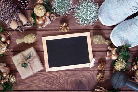 Mockup chalkboard with blank empty screen New Year resolutions fitness healthy goals concept, Christmas gift box with Xmas christmas ornaments on wood background with healthy fitness equipments