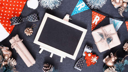 Mockup chalkboard with blank empty screen, new year gift box with Xmas pine tree model, christmas ornaments on wood background, top view, copy space place for your artwork