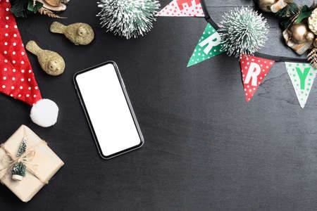 Mockup blank white screen smartphone on black desk table background for Christmas and New Year party background, Flat lay top view with copy space for your Merry Christmas and Happy New year artwork. Zdjęcie Seryjne