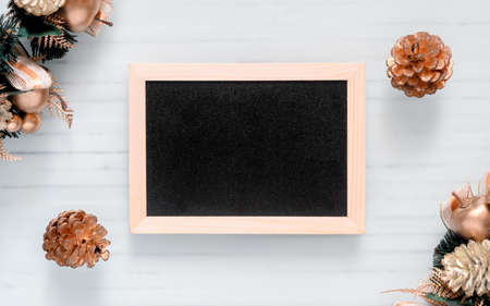 Mockup chalkboard with blank empty screen, new year gift box with Xmas pine tree model, christmas ornaments on white wood desk, top view, copy space place for your artwork Zdjęcie Seryjne