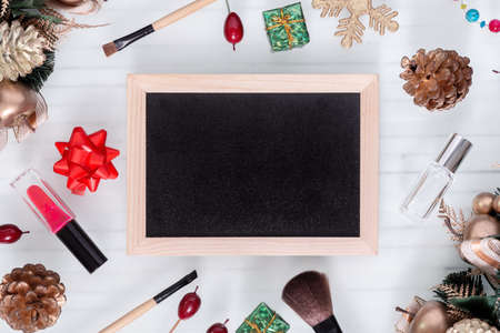 Mockup beauty Christmas New Year concept. Mock up blank empty space chalkboard with makeup cosmetic and Christmas decoration ornaments on white desk table background, top view. Zdjęcie Seryjne