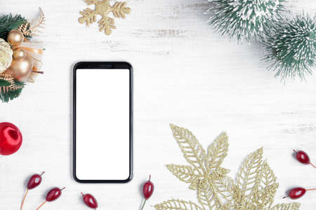 Mockup blank white screen smartphone on white wood background for Christmas and New Year party background, Flat lay top view with copy space for your Merry Christmas and Happy New year artwork.