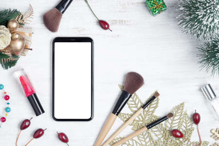 Mockup mobile phone beauty Christmas New Year concept. Mock up blank empty space smartphone with makeup cosmetic and Christmas decoration ornaments on white desk table background, top view.