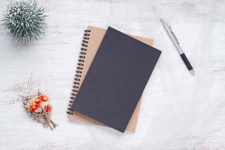 Mockup blank black book cover with pen, Christmas ornaments decor on white grunge wooden table background. Flat lay, Top view with copy space