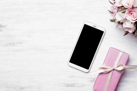 Mockup white smartphone with blank black screen on home grunge wood table background an Gift box for Christmas and New Year, Velentine's day, wedding gift concept, Mockup mobile phone with copy space. Zdjęcie Seryjne