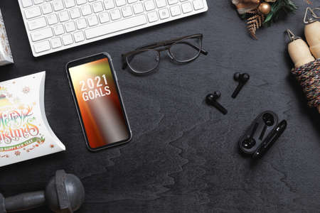 2021 New Year resolutions  healthy goals background concept. 2021 Goals text on mobile phone on table with dumbbell, jump rope, wireless earphone,  and Christmas ornaments. Mock up smartphone.
