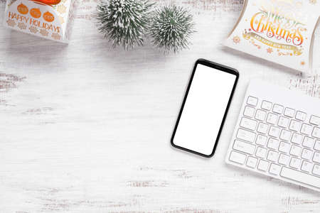 Mockup smartphone with blank white screen, new year gift box with Xmas pine tree model, christmas ornaments on grunge white wood background, top view, place for your artwork Zdjęcie Seryjne