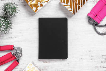 Mockup blank cover black book for New Year resolutions healthy background concept on grunge whtie Christmas ornaments and fitness equipments. Mock up blank cover black book.