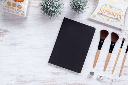 Mockup beauty Christmas New Year concept. Mock up blank empty space black cover book with makeup cosmetic and Christmas decoration ornaments on grunge white desk table background, top view.