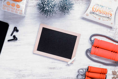 Mockup blank empty black Chalkboard for New Year resolutions healthy background concept on grunge whtie wood with Christmas ornaments and fitness equipments. Mock up blank blackboard.