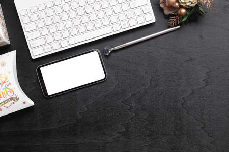 Mockup smartphone with blank white screen, new year gift box with Xmas christmas ornaments on grunge black wood hone office desk background, top view, copy space place for your artwork