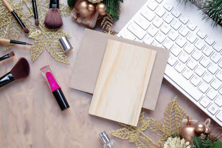 Mockup beauty Christmas New Year concept. Mock up blank empty space wood board with makeup cosmetic, Christmas decoration ornaments, New Year gifts on home office desk table background, top view.