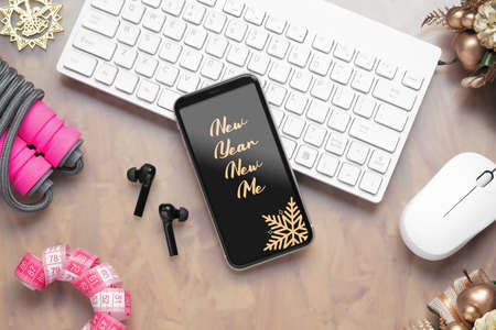 2021 New Year resolutions  healthy goals background concept. New Year New Me text on mobile phone on table with jump rope, wireless earphone,  and Christmas ornaments. Mock up smartphone.