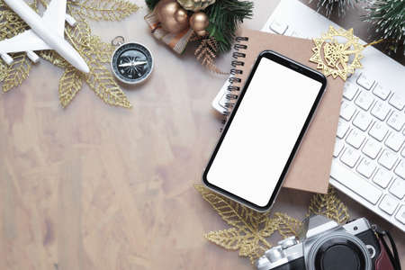 Mockup blank white screen smartphone for Christmas New Year holiday travel background concept on home office desk, Flat lay top view mock up mobile phone with plane model, camera, Xmas ornaments. Zdjęcie Seryjne