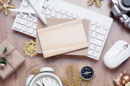 Mockup blank wood board for Christmas New Year holiday travel background concept on home office desk, Flat lay top view mock up mobile phone with plane model, camera, gift box, Xmas ornaments.