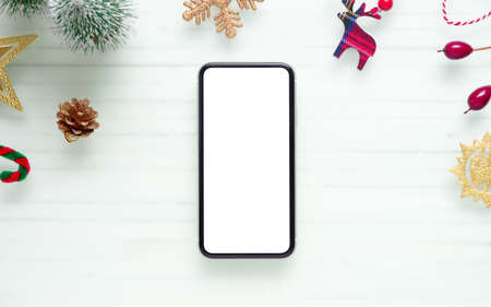Mockup blank white screen smartphone on white desk background for Christmas and New Year background concept. Mock up mobile phone.