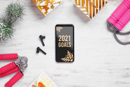 2021 New Year resolutions  healthy goals background concept. 2021 Goals text on mobile phone on table with jump rope, wireless earphone,  and Christmas ornaments. Mock up smartphone.