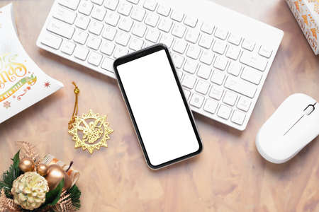 Mockup blank white screen smartphone on home office desk background for Christmas and New Year background concept, Flat lay top view with copy space for your Merry Christmas and Happy New year artwork.