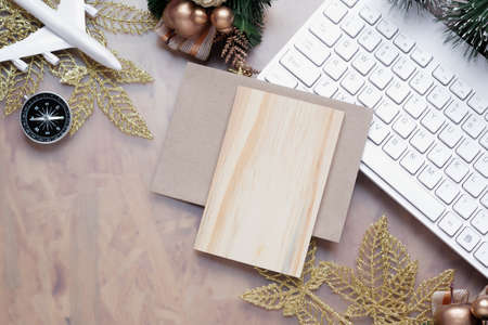 Mockup blank wood board for Christmas New Year holiday travel background concept on home office desk, Flat lay top view mock up wooden greeting card with plane model and Xmas ornaments. Zdjęcie Seryjne