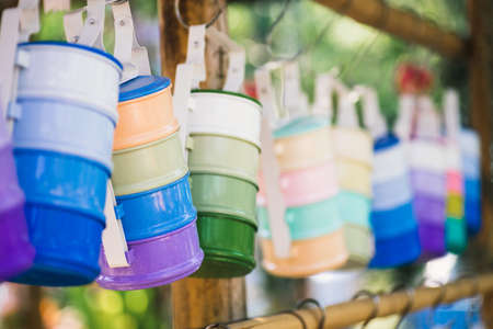 Still life with multicolored food carrier or tiffin carrier hanging on the wood stick. Selective focus vintage retro Thai style colorful tiffin carrier. Shallow DoF. Stok Fotoğraf
