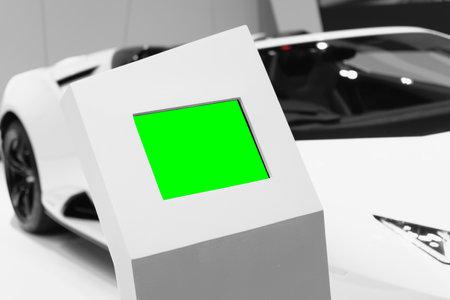 Mockup blank green screen digital LED billboard with blurred sport car background. Mock up blank screen for your advertisement artwork.