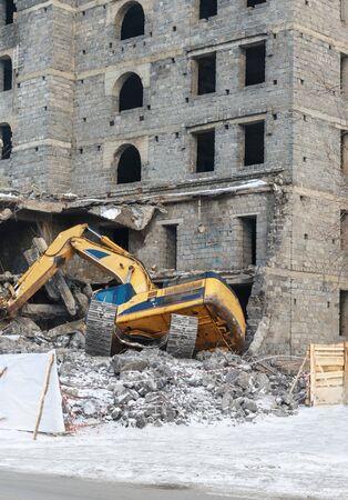 derrumbe: explosión, bomba, construcción, niveladora, colapso, se derrumbó, accidente, cavador derribado la estructura del edificio de invierno construcción de la cerca de la oruga Foto de archivo