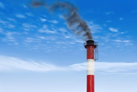 big pipe and black smoke against the blue sky Stock Photo