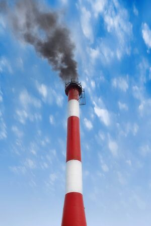condensers: big pipe and black smoke against the blue sky Stock Photo
