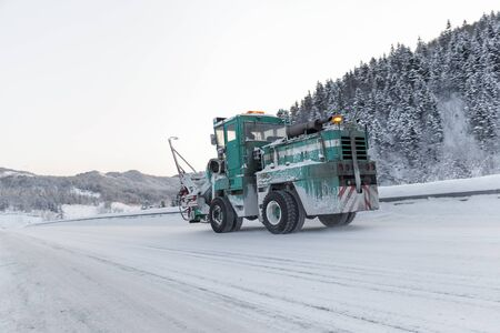 machine cleans snow from the road