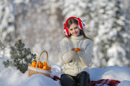 A young girl walks in the winter forest with a basket of mandarin. Stock Photo