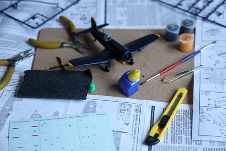 avocation: A blue plane model set up, plan and tools are on the table