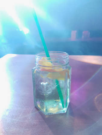 A glass of cocktail with straw, lemon and cubes of ice placed on table in the night bar, restaurant while disco lights shining on cocktail. Stock Photo