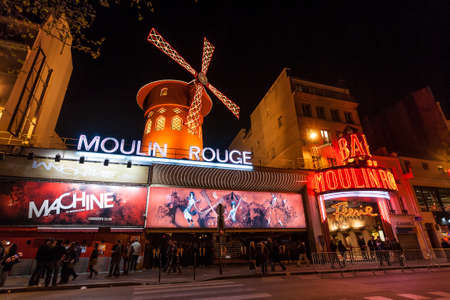 moulin: PARIS - June 25  The Moulin Rouge at night, on June 25, 2013 in Paris, France  Moulin Rouge is a famous cabaret built in 1889,  locating in the Paris red-light district of Pigalle