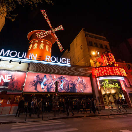 moulin: PARIS - June 25: The Moulin Rouge at night, on June 25, 2013 in Paris, France. Moulin Rouge is a famous cabaret built in 1889,  locating in the Paris red-light district of Pigalle.