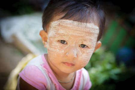 YANGON - MYANMAR - November 15, 2013: Unidentified Burmese boy with thanaka on his face on November 15, 2013 in Yangon, Myanmar. Thanaka is a yellowish-white cosmetic paste made from ground bark.