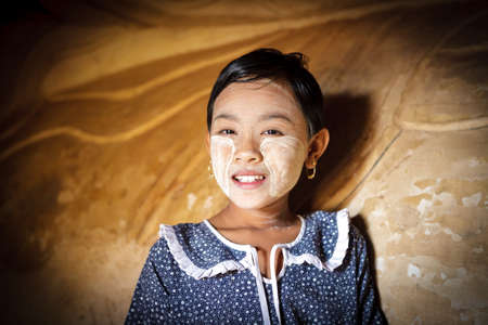 YANGON - MYANMAR - November 15, 2013: Unidentified Burmese girl with thanaka on her face on November 15, 2013 in Yangon, Myanmar. Thanaka is a yellowish-white cosmetic paste made from ground bark.