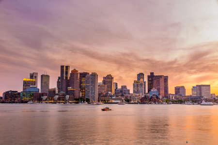 Boston downtown skyline panorama with skyscrapers over water at twilight photo
