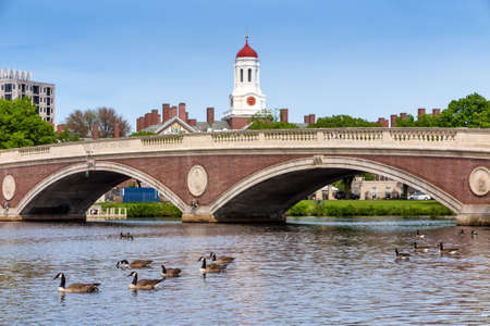 harvard university: John W. Weeks Bridge and clock tower over Charles River in Harvard University campus in Boston with trees, boat and blue sky. Editorial